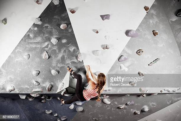 Female climber scaling climbing wall
