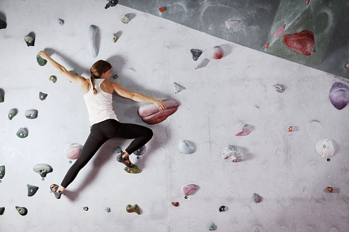 Female climber scaling climbing wall - gettyimageskorea