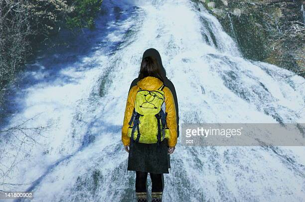 Female climber standing in front of waterfall