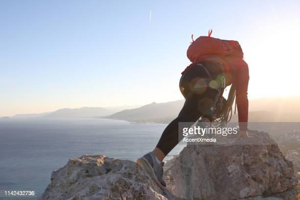scalatrice donna si estende attraverso rocce di cima al tramonto - vivere semplicemente foto e immagini stock
