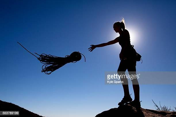A female climber throws a rope off Lower Gibraltar Rock in Santa Barbara, California. Lower Gibraltar Rock provides great vistas of Santa Barbara and the Pacific Ocean.