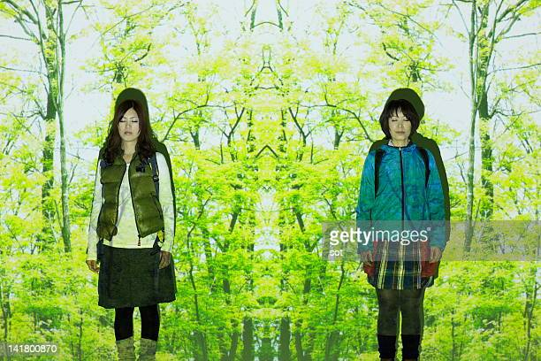 Female Climbers standing in front of green forest