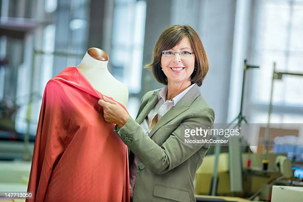 female clothes designer smiling with draping mannequin - fashion industry stock pictures, royalty-free photos & images