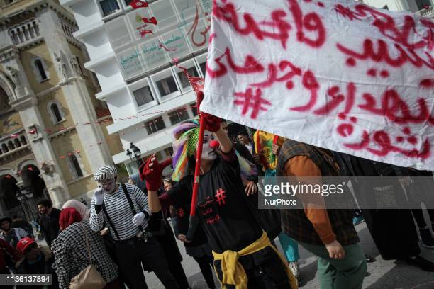 """Female clown from the """"Brigade of Activist Clowns"""" (French: Brigade des Clowns Activistes"""" waving a flag that reads in Arabic 'release..."""