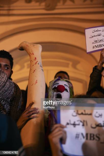 A female clown holds a leg of a doll with traces of blood representing the murdered Saudi journalist Jamal Khashoggi as she took part in a...