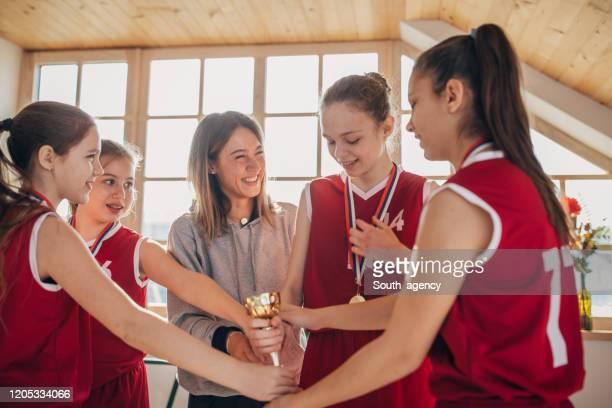coach donna che festeggia la vittoria con la squadra di basket - sport di squadra foto e immagini stock