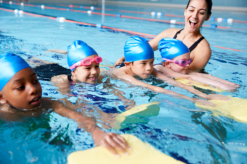 Female Coach In Water Giving Group Of Children Swimming Lesson In Indoor Pool 1167733673