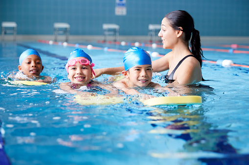 Female Coach In Water Giving Group Of Children Swimming Lesson In Indoor Pool 1167733771