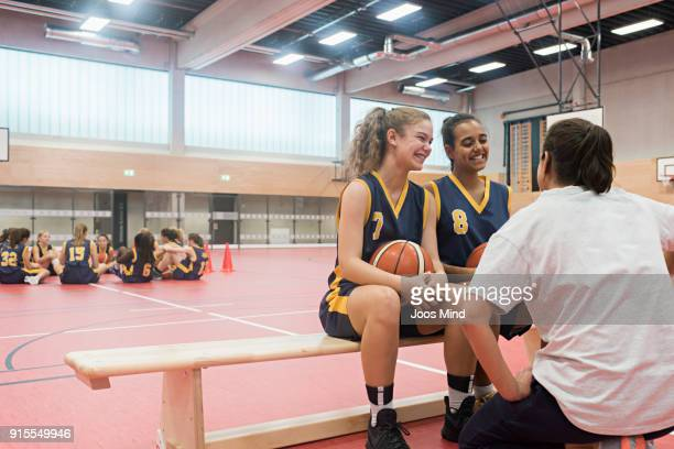 female coach motivates two young basketball players - court hearing stockfoto's en -beelden