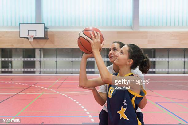 Female coach teaching basketball exercises