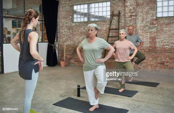 female coach teaching yoga to seniors at gym - standing on one leg stock pictures, royalty-free photos & images
