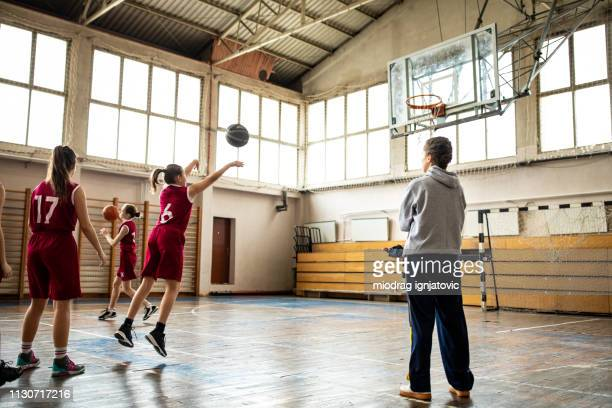 female coach watching teenage girls practicing free throws - making a basket scoring stock pictures, royalty-free photos & images