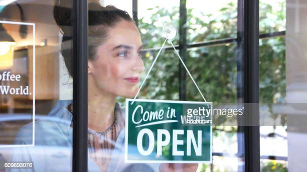 Female coffee shop owner opening the shop