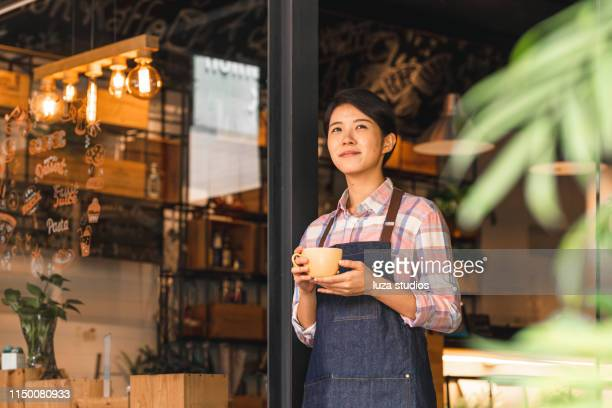 female coffee shop owner standing confidently in front of her cafe - tea room stock pictures, royalty-free photos & images