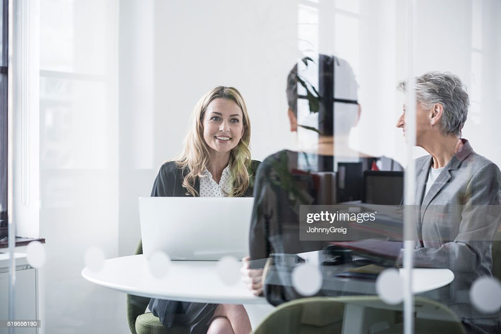 Female colleagues behind glass screen in meeting room : Stock Photo