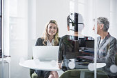 Female colleagues behind glass screen in meeting room