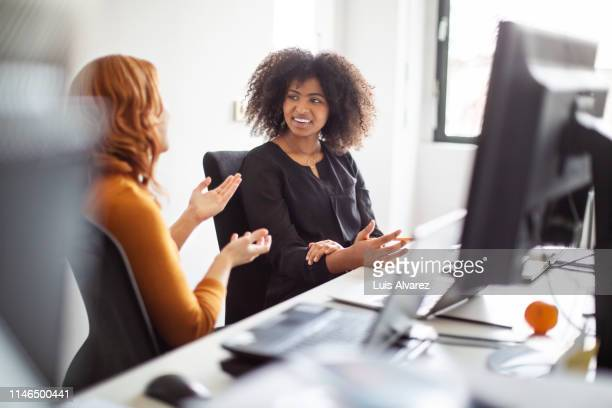 female colleagues discussing over new project - close to stock pictures, royalty-free photos & images