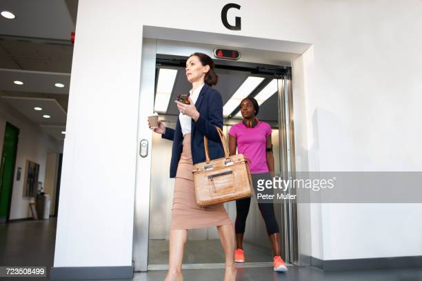 Female colleagues exiting office lift