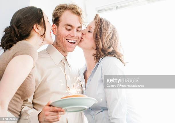 Female colleagues kissing man on cheek with birthday cake