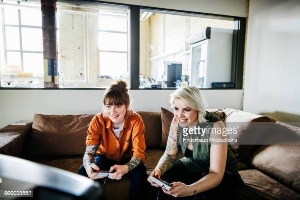 Female colleagues playing old video game in office