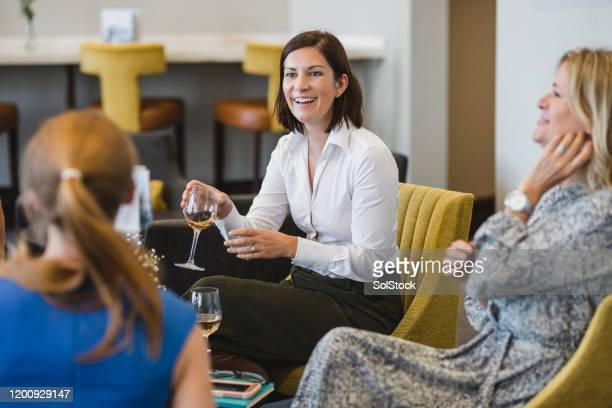 female colleagues relaxing with wine after corporate event - real life stock pictures, royalty-free photos & images