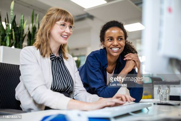 female colleagues smiling while looking at computer - colleague photos et images de collection