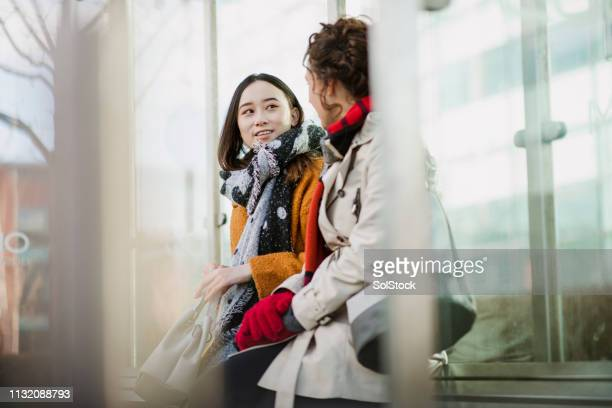 female colleagues waiting for the bus - public transport stock pictures, royalty-free photos & images