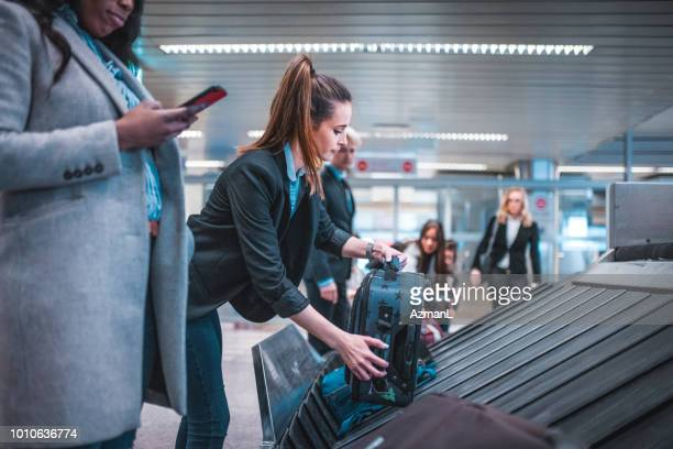 female colleagues with luggage on conveyor belt - baggage claim stock pictures, royalty-free photos & images