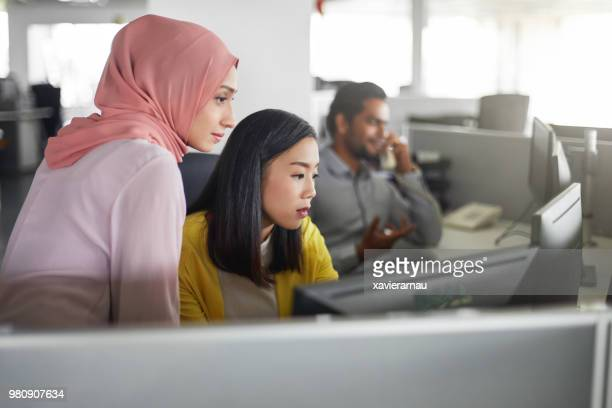 female colleagues working at computer desk - multiracial group stock pictures, royalty-free photos & images