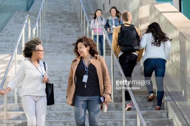 female college professors walk together on campus - community college stock pictures, royalty-free photos & images