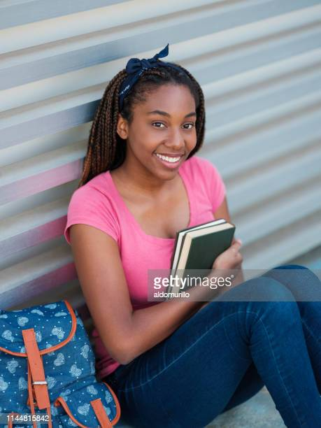female college student hugging books while sitting - medium shot stock pictures, royalty-free photos & images