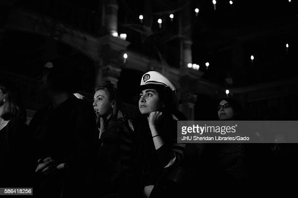 A female college student in a sailor hat looks toward the stage as she sits among other audience members at the Johns Hopkins University 2015...
