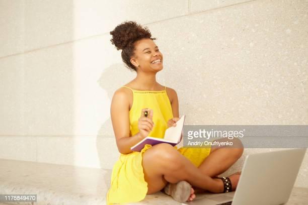 female college student learning outdoor - gelbes kleid stock-fotos und bilder