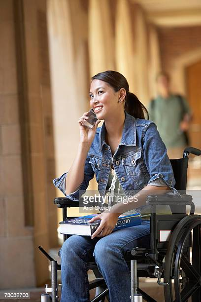 Female college student on wheelchair talking on phone in corridor
