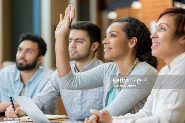 female college student raises hand during class - hand raised stock pictures, royalty-free photos & images