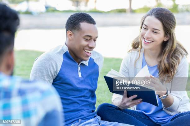 Female college student reads book with friends