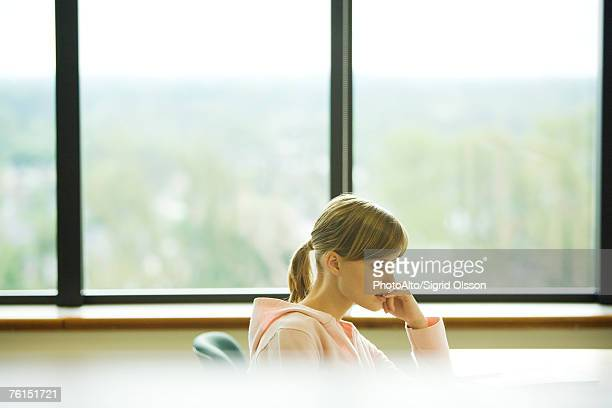 """female college student sitting in front of window, biting finger"" - erker stockfoto's en -beelden"