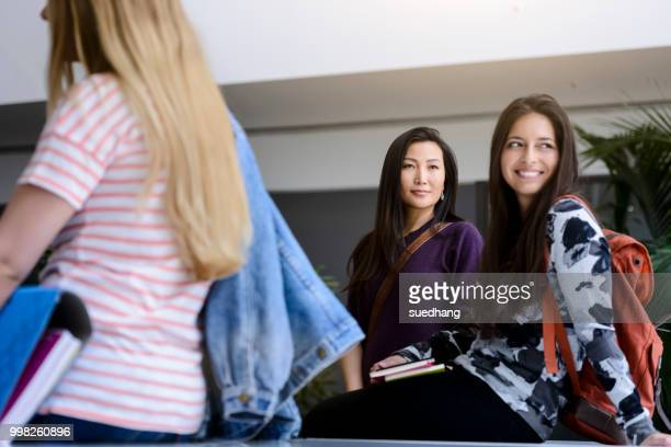 Female college student sitting on table in classroom