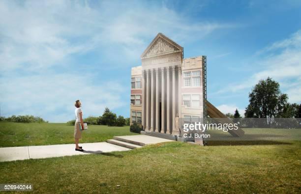 female college student stands in front of flat facade of college building - künstlich stock-fotos und bilder