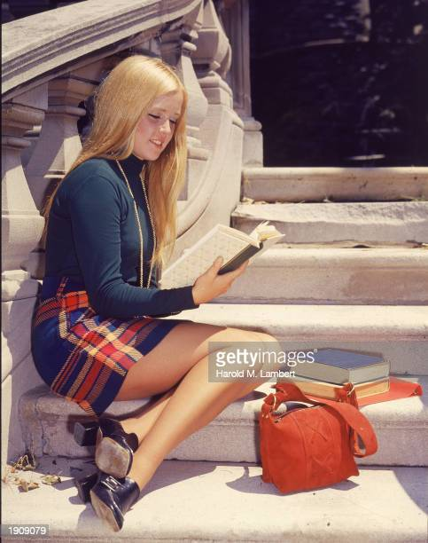 A female college student wearing a plaid miniskirt sits on a flight of steps and studies her textbook early 1970s
