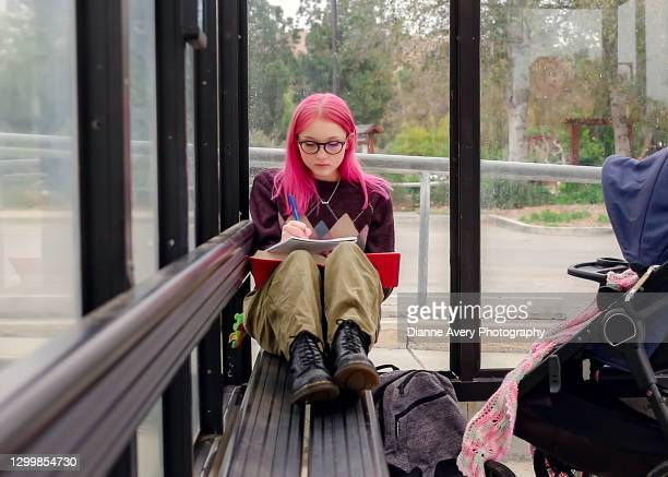female college student with stroller at bus stop - thousand oaks stock pictures, royalty-free photos & images