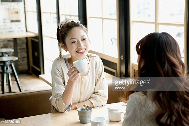 Female college students discuss in a cafe