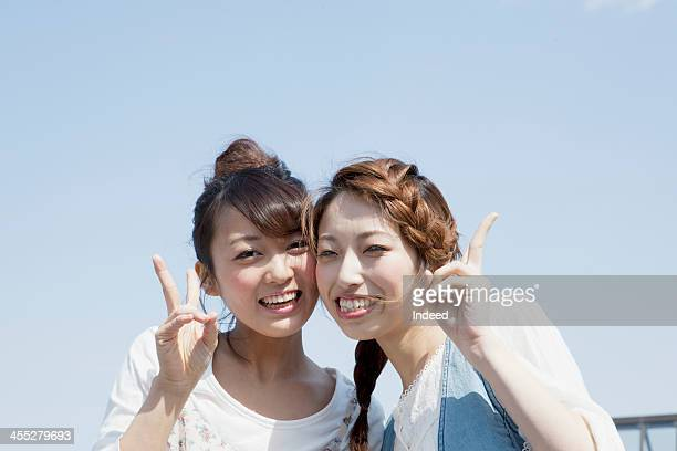 Female college students frolic under a blue sky