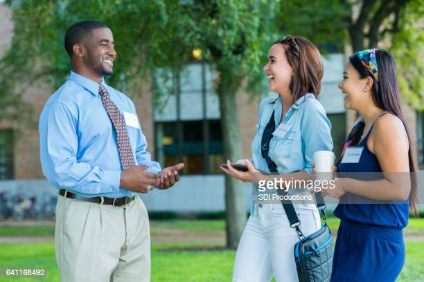 Female college students talk with campus tour guide