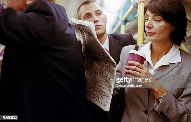 female commuter reading newspaper - femmes d'âge moyen photos et images de collection