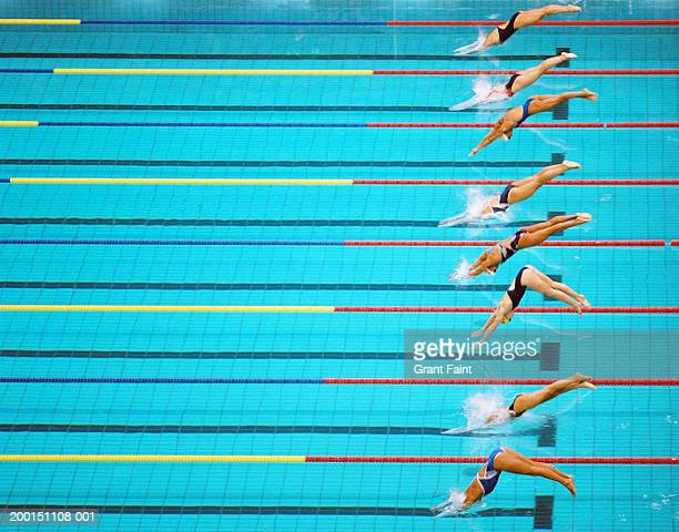 Female competition swimmers diving into pool, elevated view, side view