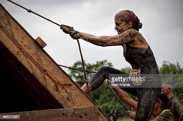 CONTENT] A female competitor at at the Rugged Mania obstacle course climbs a wooden wall