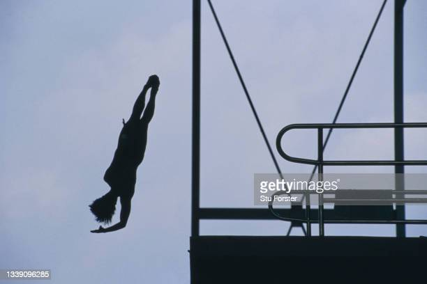 Female competitor is silhouetted against the sky whilst performing her routine diving in the Women's 10-metre springboard diving competition during...