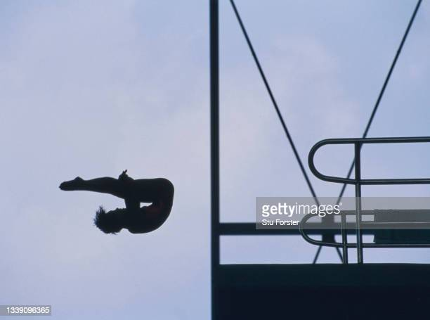 Female competitor is silhouetted against the sky whilst performing her routine dive in the Women's 10-metre Springboard diving competition during the...