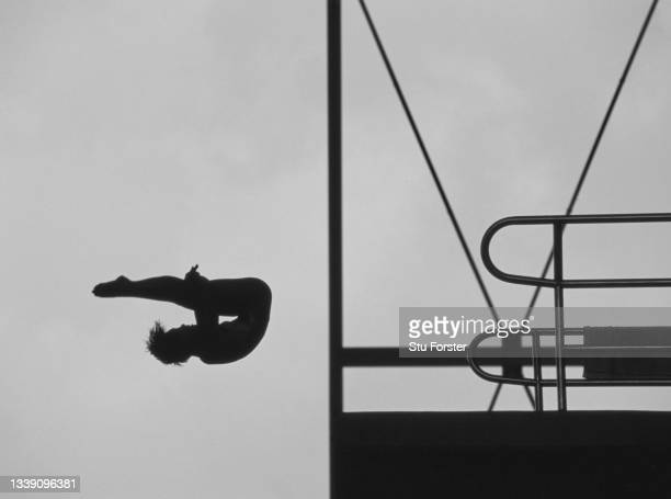 This image has been converted to black and white), A female competitor is silhouetted against the sky whilst performing her routine diving in the...
